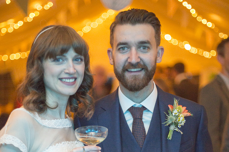 photo of a cool hipster wedding couple at their reception smiling to camera