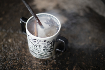 mug of boiling cider on ground with red hot poker in it and spices floating.